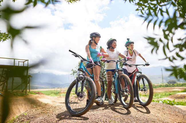 Women friends mountain biking on sunny obstacle course trail — Stock Photo