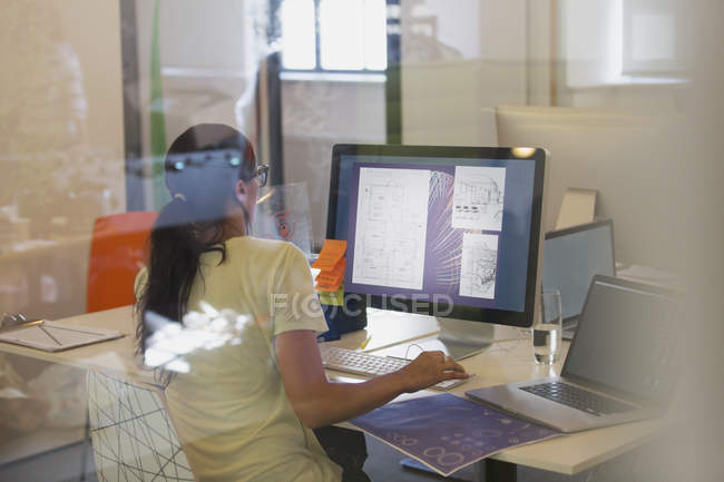 Женщина-дизайнер с помощью компьютера в офисе — стоковое фото