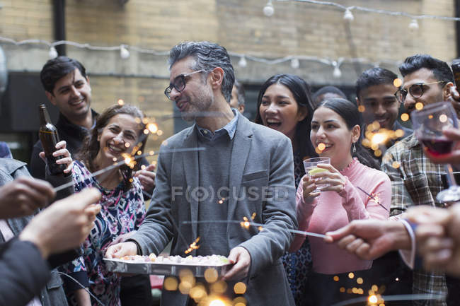 Friends with sparklers celebrating with man holding birthday cake — Stock Photo