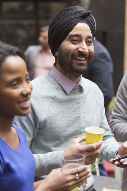 Homme en turban appréciant parti souriant — Photo de stock