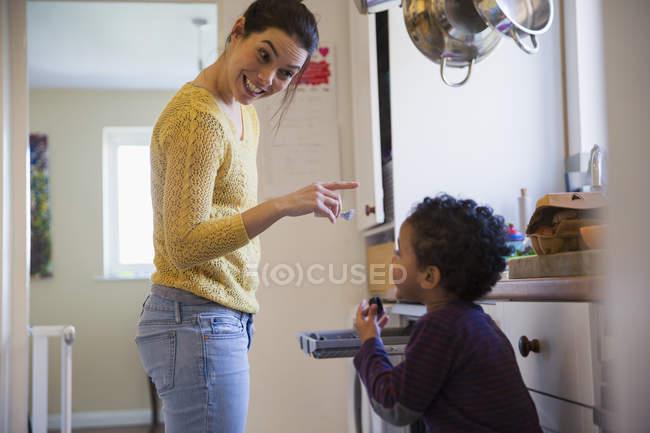 Счастливая мать кавказской с афро-американских сына на кухне — стоковое фото