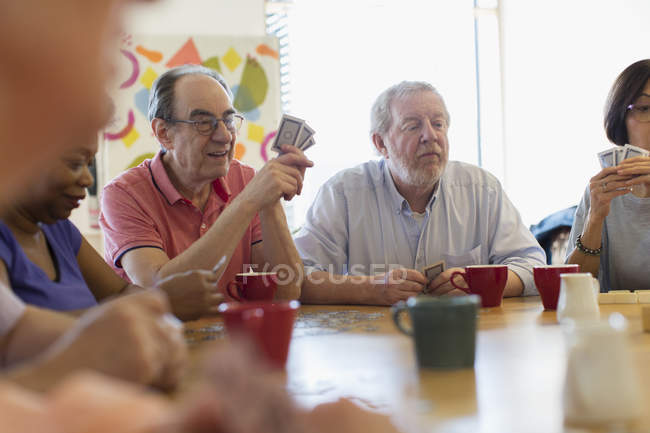 Senior friends playing cards and drinking tea in community center — Stock Photo