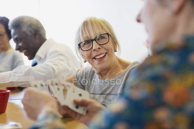 Smiling senior woman playing cards with friend in community center — Stock Photo