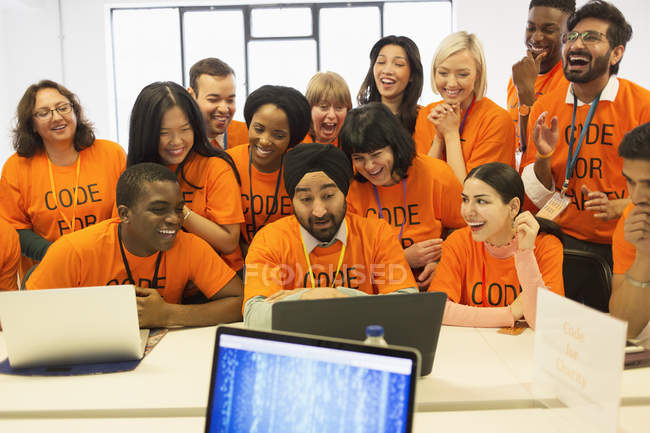 Happy hackers sharing laptop, coding for charity at hackathon — Stock Photo