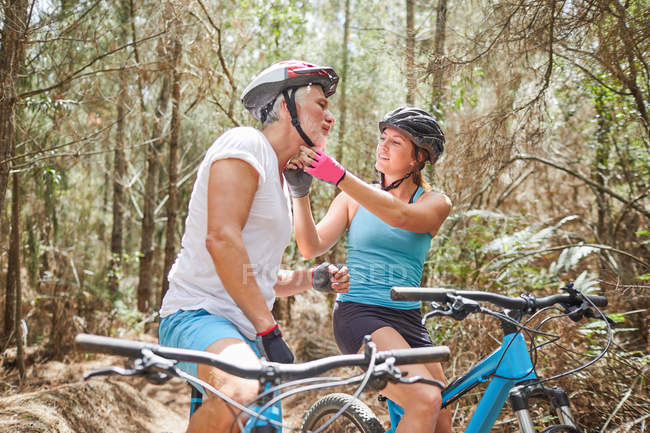 Daughter helping father with mountain biking helmet on trail in woods — Stock Photo