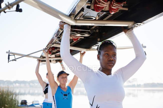 Selbstbewusst, bestimmt weibliche Rudern team heben Scull overhead — Stockfoto