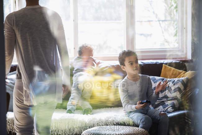 Menino com controle remoto assistindo TV na sala de estar — Fotografia de Stock