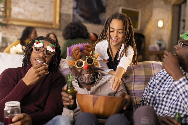 Playful multi-generation family wearing Christmas glasses, enjoying popcorn — Stock Photo