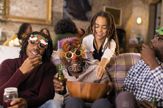 Famiglia di diverse generazioni giocoso con gli occhiali di Natale, godendo di popcorn — Foto stock