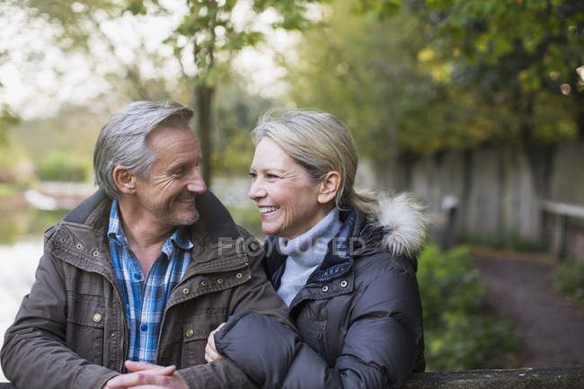 Mature caucasian couple standing by fence together in autumn park — Stock Photo