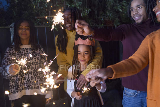 Family celebrating with sparklers — Stock Photo