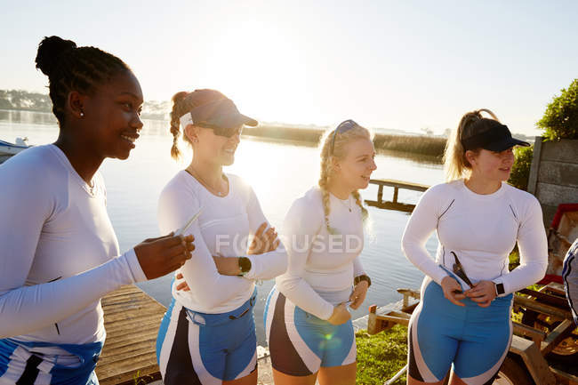 Female rowing team standing at sunny lakeside — Stock Photo