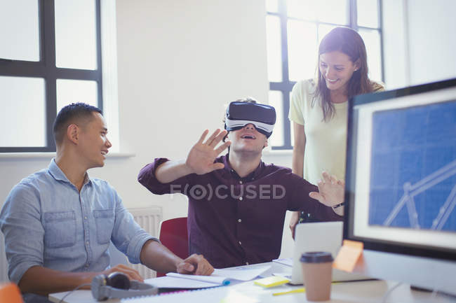 Computer programmers testing virtual reality simulator glasses in office — Stockfoto