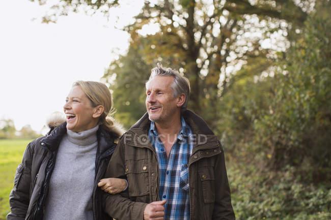 Зрелая кавказская пара, гуляющая вместе в осеннем парке — стоковое фото