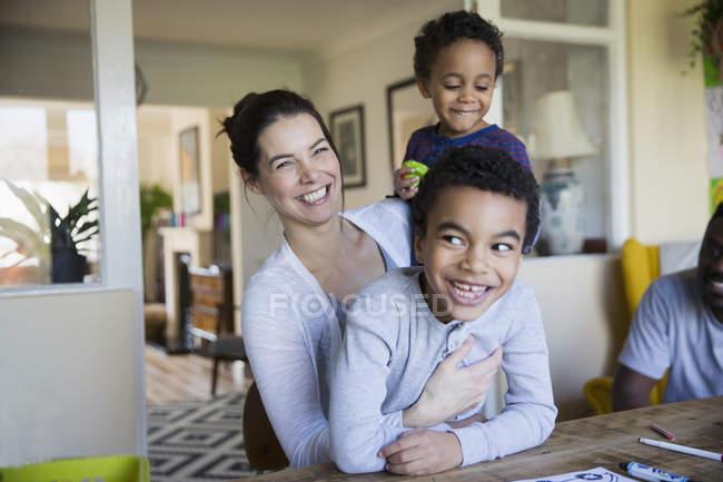 Retrato feliz madre e hijos en mesa de comedor - foto de stock