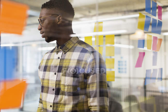 Creative businessman brainstorming, using adhesive notes at office window — Stock Photo