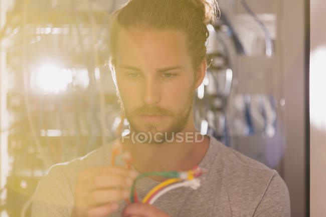 Focused IT technician examining connection plugs in server room — Stock Photo