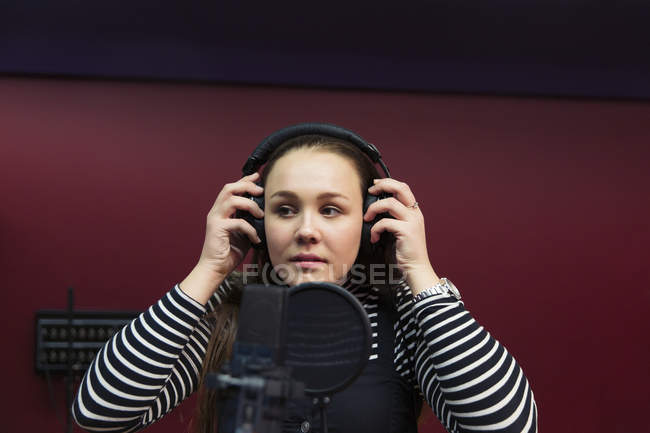Teenage girl musician recording music, singing in sound booth — Stock Photo