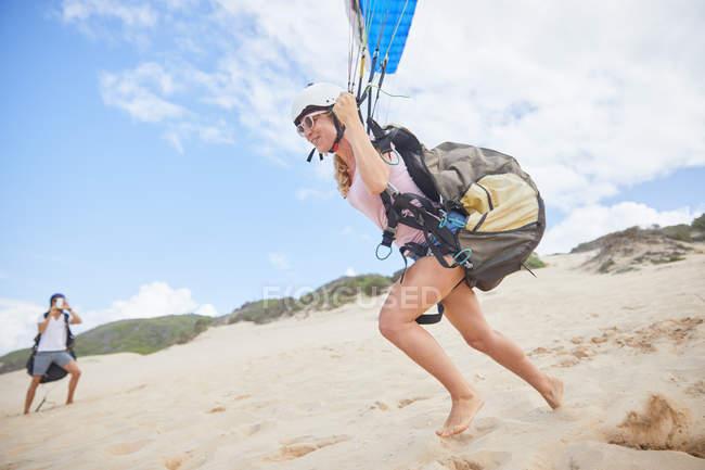 Feminino parapente correndo, decolando na praia — Fotografia de Stock