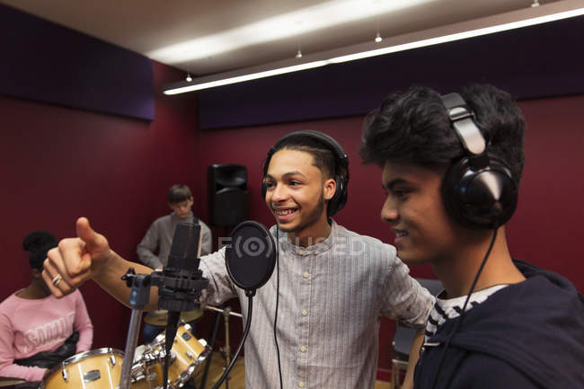 Smiling teenage musicians recording music, singing in sound booth — Stock Photo