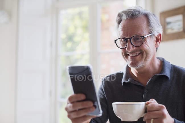 Homem maduro sorridente bebendo chá e usando telefone inteligente — Fotografia de Stock