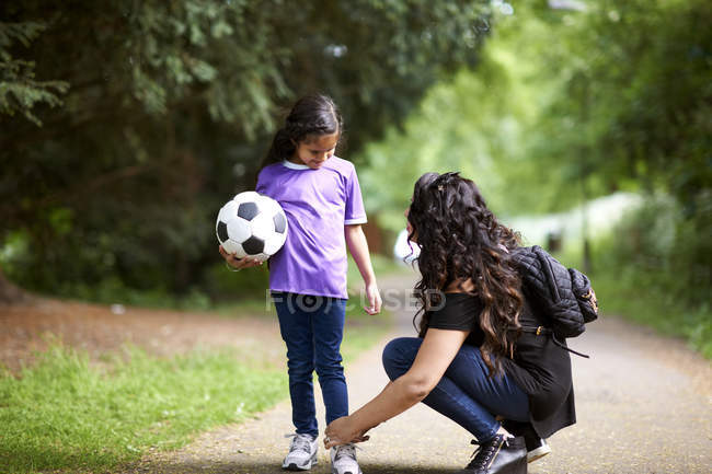 Mère attachant lacet de chaussure de fille tenant ballon de football — Photo de stock