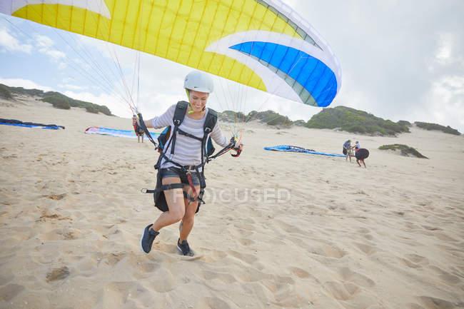 Parapendio femminile con paracadute in corsa, decollo in spiaggia — Foto stock