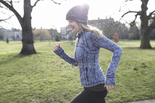 Улыбающаяся бегунья бегает в солнечном парке — стоковое фото