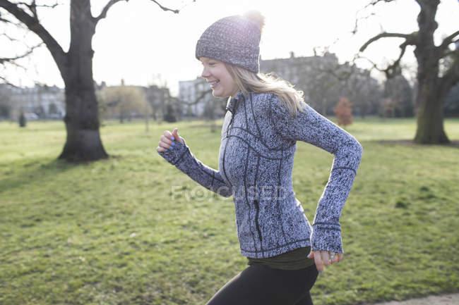 Corridente corridore femminile in esecuzione nel parco soleggiato — Foto stock