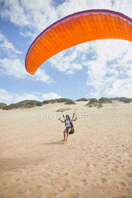 Male paraglider running with parachute on beach — Stock Photo