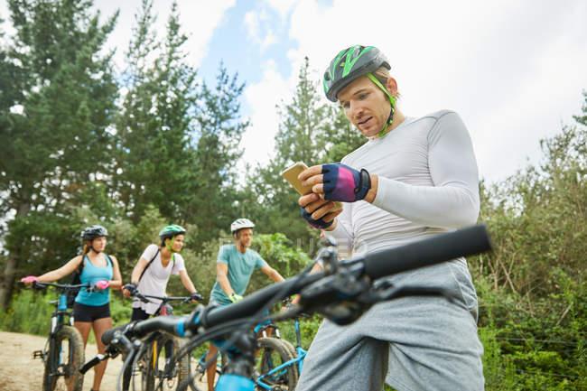 Man mountain biking, using smart phone in woods — Stock Photo