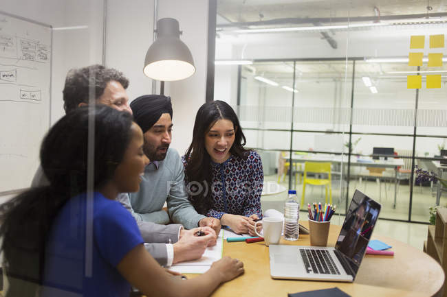 Creative business people video conferencing at laptop in conference room — Stock Photo