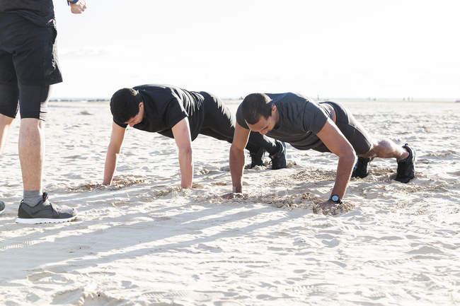 Чоловіків робити віджимання на сонячному пляжі — стокове фото