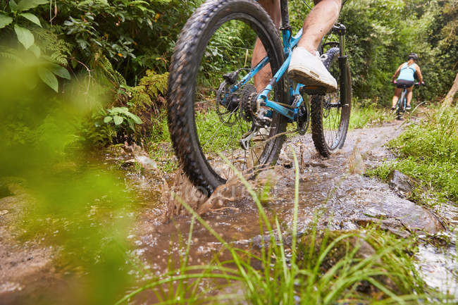 Man mountain biking, riding through puddle in woods — Stock Photo