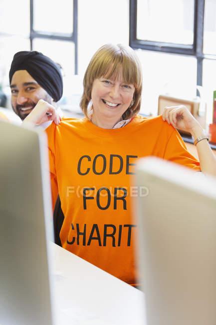 Portrait hacker confiant portant t-shirt, codage pour la charité au hackathon — Photo de stock