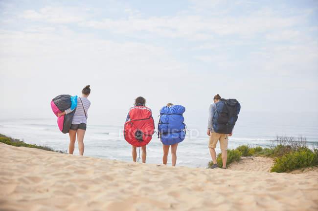 Parapentes carregando mochilas de para-quedas na praia do oceano — Fotografia de Stock