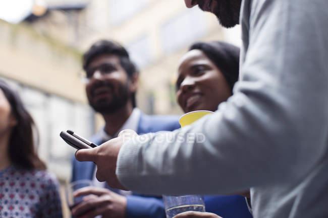 Hombre mensajes de texto con el teléfono inteligente en la fiesta - foto de stock