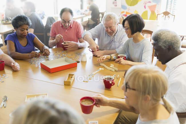 Seniorenfreunde spielen am Tisch im Bürgerhaus — Stockfoto