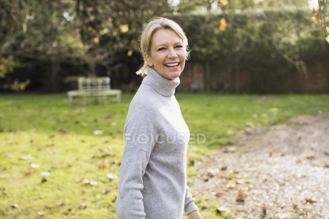 Портрет счастливой блондинки в сером свитере в саду — стоковое фото