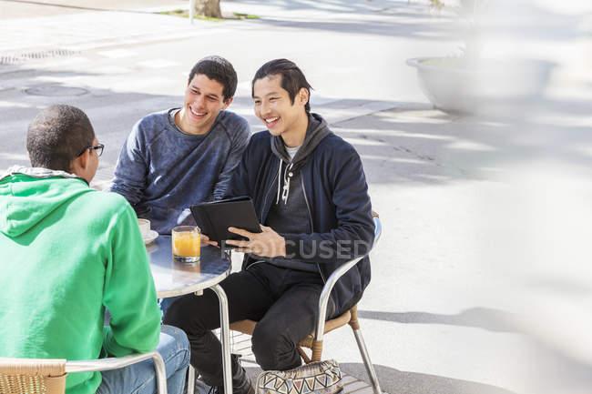 Усміхнений чоловік друзі говорили в сонячному тротуару кафе — стокове фото