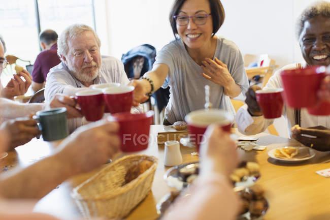 Щасливі старший друзів, насолоджуючись післяобідній чай, тостів кружки в общинний центр — Stock Photo