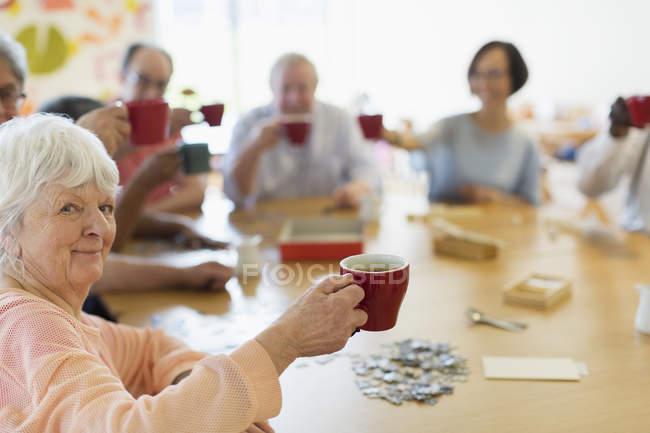 Портрет щасливі старший жінка, насолоджуючись післяобідній чай з друзями в общинний центр — Stock Photo