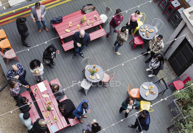 Overhead view friends socializing, drinking and eating at party on patio — Stock Photo
