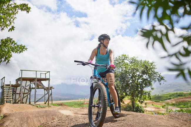 Woman mountain biking at sunny obstacle course — Stock Photo