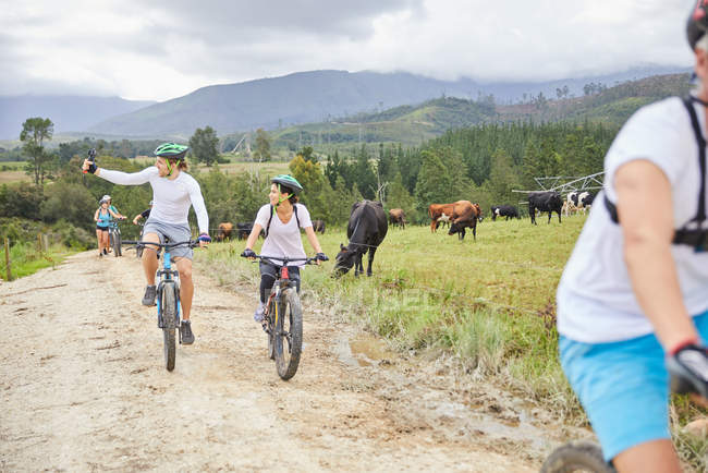Friends mountain biking on rural dirt road along cow pasture — Stock Photo