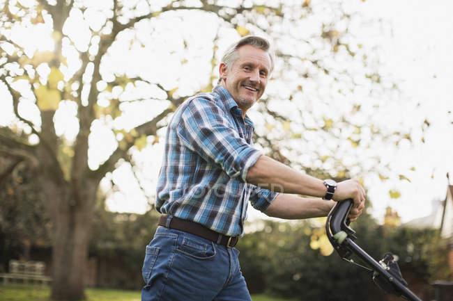 Mature caucasian man with grass-cutter working in garden — Stock Photo