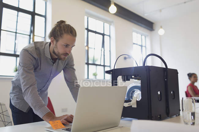 Male designer working at laptop next to 3D printer in office — Stock Photo