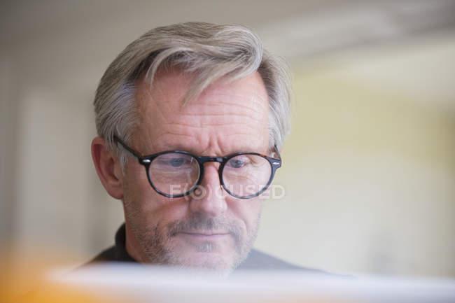 Focalisé homme mûr dans les lunettes de travail à l'ordinateur portable — Photo de stock