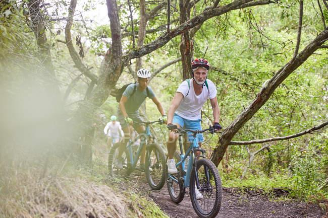 Men mountain biking on trail in woods — Stock Photo