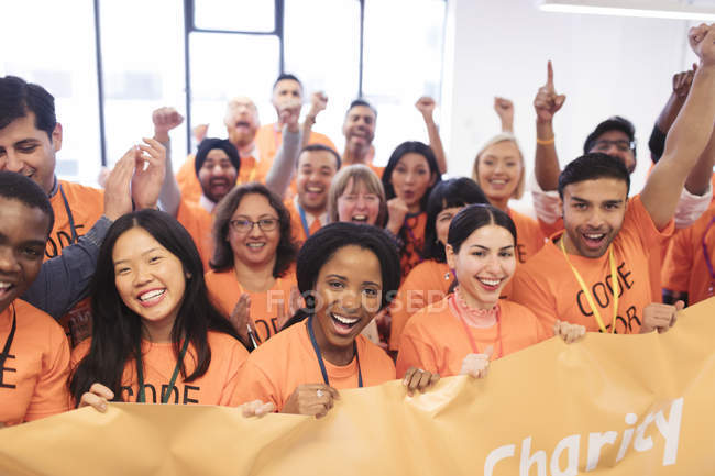 Happy hackers with banner cheering, coding for charity at hackathon — Stock Photo